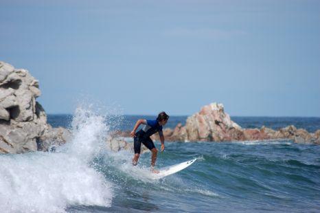 Un surfista sorteando las piedras