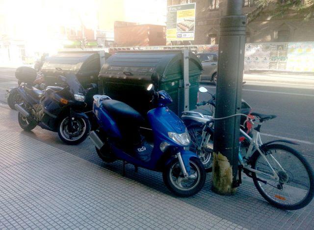 Motos y bicis junto a los contenedores