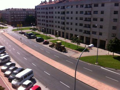 Excavadora aparcada entre coches